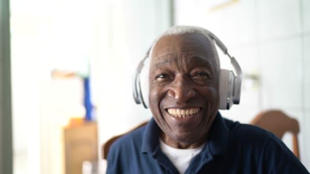 portrait of senior man listening music at home - headphones stock videos & royalty-free footage