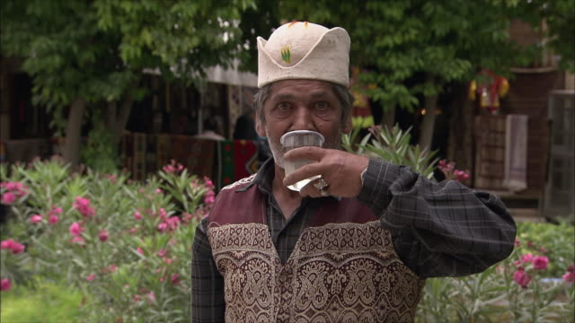 cu portrait of senior man pouring water from large tea pot into plastic cup and drinking outdoors, iran - tea pot stock videos and b-roll footage