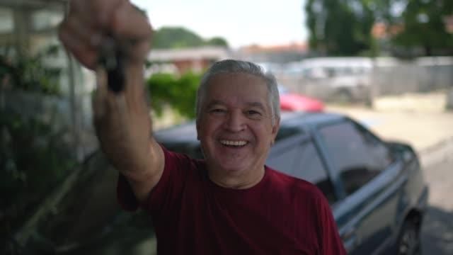 車のキーを示す先輩男性の肖像画 - 車のキー点の映像素材/bロール