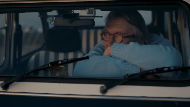 portrait of senior man sitting in his car enjoying sunset - active seniors stock videos & royalty-free footage