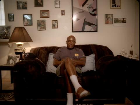 ws, portrait of senior man sitting on couch in living room, reno, nevada, usa - full length点の映像素材/bロール