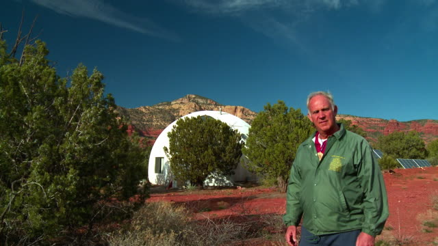 ms portrait of senior man standing near domed house behind trees, sedona, arizona, usa - dreiviertelansicht stock-videos und b-roll-filmmaterial