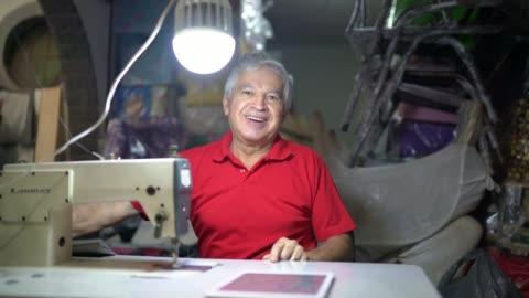 vidéos et rushes de verticale d'homme aîné utilisant une machine à coudre dans l'atelier de tapisserie - 65 69 ans