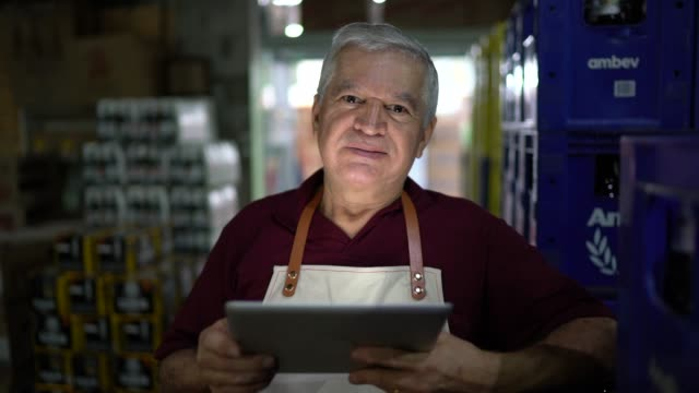 portrait of senior man using digital tablet at warehouse - owner stock videos & royalty-free footage