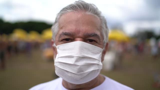 porträtt av äldre man med ansiktsmask i ett offentligt evenemang - kirurgmask bildbanksvideor och videomaterial från bakom kulisserna