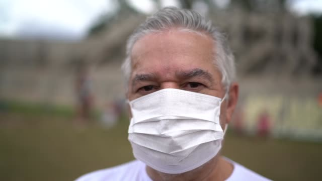portrait of senior man with facial mask in a public event - etnia latino americana video stock e b–roll