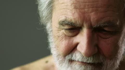 slo mo ecu portrait of senior man with gray beard in studio / new york city, new york state, usa - sorgsenhet bildbanksvideor och videomaterial från bakom kulisserna