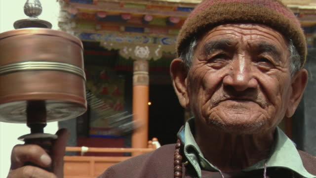 CU, Portrait of senior man with prayer wheel at Likir Monastery, Ladakh, Jammu and Kashmir, India