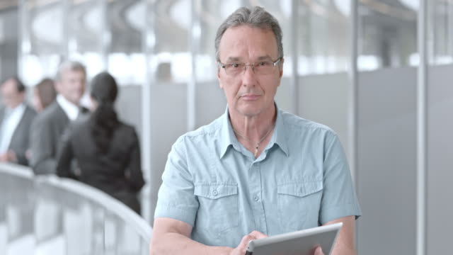 SLO MO DS Portrait of senior man working with tablet