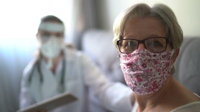 vídeos y material grabado en eventos de stock de retrato de paciente senior en consulta médica en su casa - visita