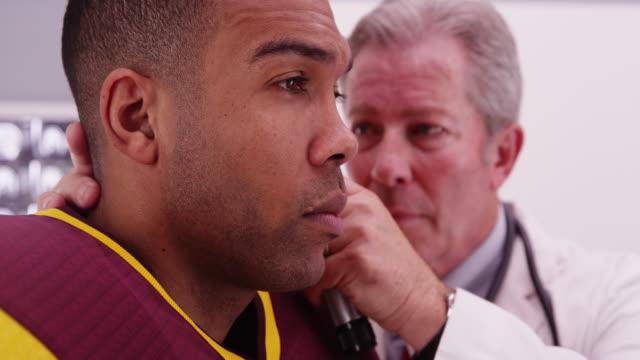 vídeos y material grabado en eventos de stock de portrait of senior white doctor checking black sports athlete's ear - cuello humano