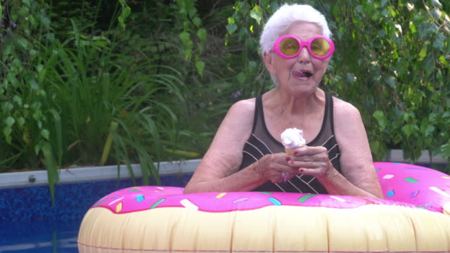 portrait of senior woman enjoying ice cream by the pool summer festive attitude - eccentric stock videos & royalty-free footage