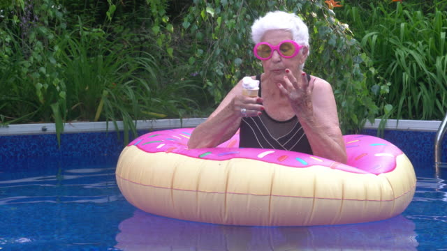 portrait of senior woman enjoying ice cream by the pool summer festive attitude - swimming pool stock videos & royalty-free footage