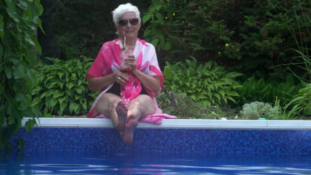 portrait of senior woman enjoying life by the pool side summer festive attitude - smooth stock videos & royalty-free footage