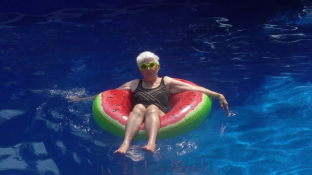 portrait of senior woman enjoying life by the pool summer festive attitude - swimming pool stock videos & royalty-free footage