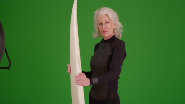 portrait of senior woman in wetsuit holding surfboard on greenscreen - old diving suit stock videos and b-roll footage