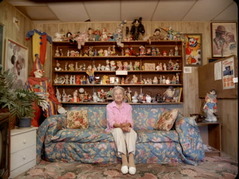 ws, portrait of senior woman sitting on couch with shelves of clown figurines in background, tonopah, nevada, usa - 集める点の映像素材/bロール