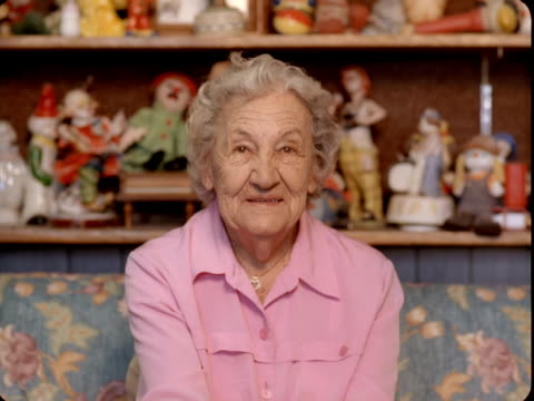 cu, portrait of senior woman sitting on couch with shelves of clown figurines in background, tonopah, nevada, usa - 集める点の映像素材/bロール