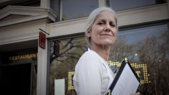 ms la portrait of senior woman smiling, holding menus, standing outside restaurant - 60 64 years stock videos & royalty-free footage