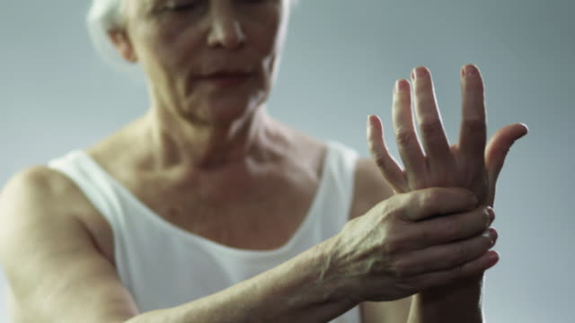 vidéos et rushes de slo mo ms pan r/f portrait of senior woman squeezing her hand in studio / new york city, new york state, usa - arthrite