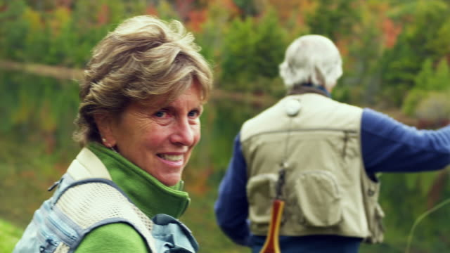 MS PAN Portrait of senior woman standing behind man fly fishing on lake edge, Manchester, Vermont, USA