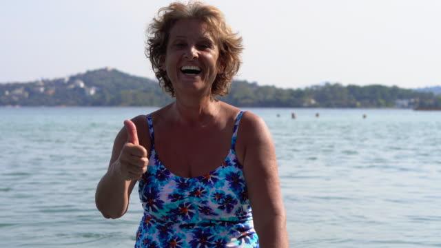 vídeos de stock, filmes e b-roll de retrato do surfista mulher sênior no mar - roupa de natação