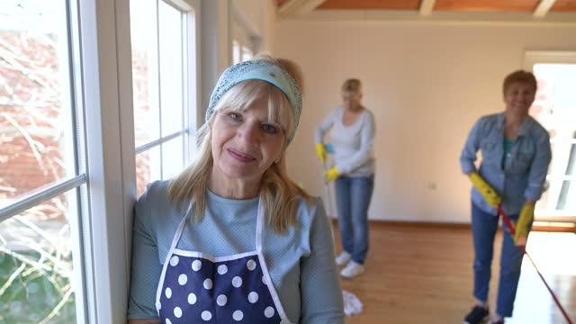 vídeos y material grabado en eventos de stock de retrato de una mujer mayor mientras limpia su casa con sus amigos - cinta de cabeza