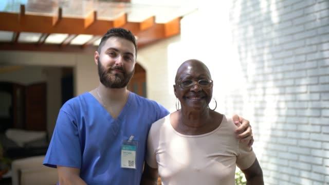 vídeos de stock e filmes b-roll de portrait of senior woman with home caregiver - social worker