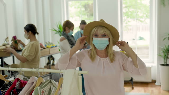 vídeos de stock e filmes b-roll de portrait of senior woman with protective face mask in clothing store - viciado em compras