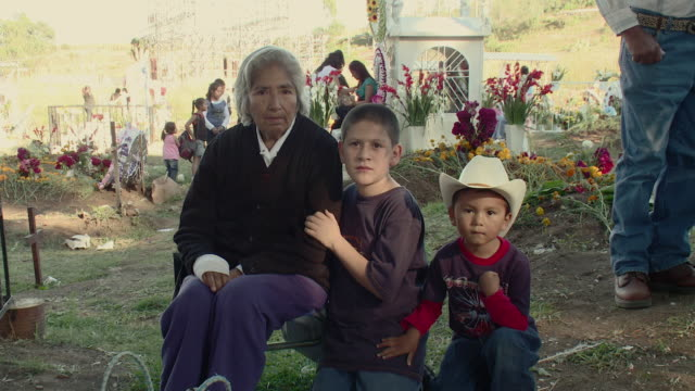 MS Portrait of senior woman with two grandsons sitting in graveyard / Lagunillas, Michoacan, Mexico