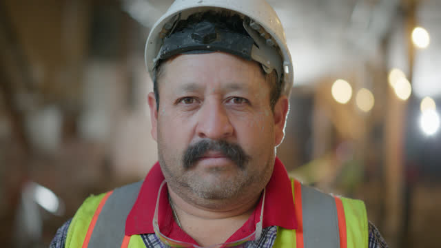 slo mo portrait of serious construction worker at a construction site - blinking stock videos & royalty-free footage