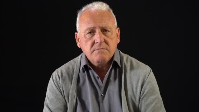 porträt von ernster mann vor schwarzem hintergrund - schwarzer hintergrund stock-videos und b-roll-filmmaterial