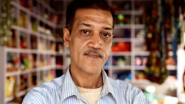 cu portrait of serious salesman standing in shop / delhi, india - blank expression stock videos & royalty-free footage