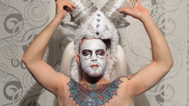 vídeos y material grabado en eventos de stock de cu portrait of shirtless man with stage make-up and contact lenses putting on faun horns / miami, florida, usa - escenario