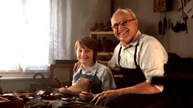 HD DOLLY: Portrait de cordonnier avec jeune apprenti