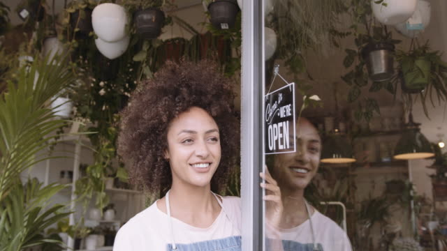 portrait of small business entrepreneur afro american female store owner turning open sign in shop doorway and smiling - information sign stock videos & royalty-free footage