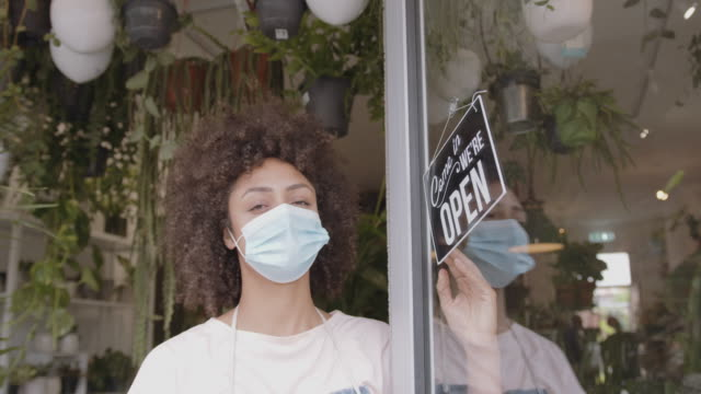 stockvideo's en b-roll-footage met portrait of small business entrepreneur afro american female store owner turning open sign in shop doorway wearing face mask during coronavirus pandemic - etalage
