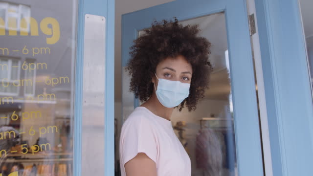 portrait of small business entrepreneur afro american female store owner in shop doorway and looking to camera - doorway stock videos & royalty-free footage