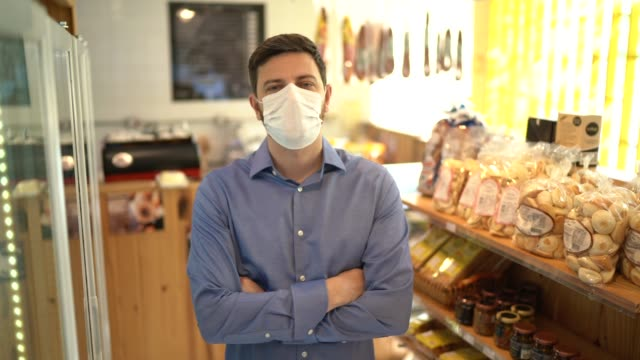 vídeos de stock e filmes b-roll de portrait of small business man owner with face mask - vender