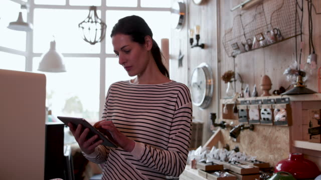 portrait of small business owner holding digital tablet in a home store - antique stock videos & royalty-free footage
