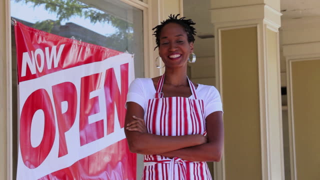 ms pan portrait of small business owner in front of shop with now open sign in window / richmond, virginia, united states - now open stock videos & royalty-free footage