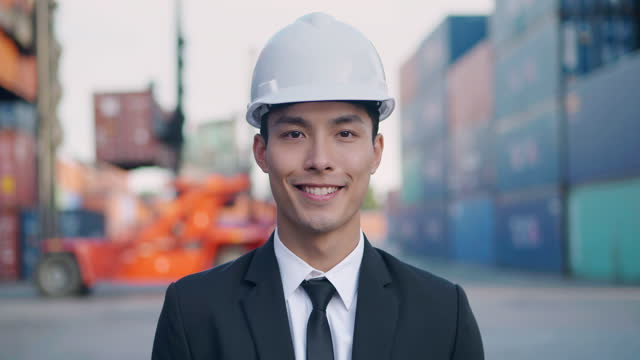 portrait of smile asian businessman or engineer age 27 yearold looking at camera of confidence at commercial transport background.pride in work concept. - jetty stock videos & royalty-free footage