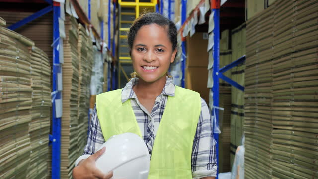 portrait of smile young women of african american ethnicity age 28 yearold while take off the helmet while looking at camera of confidence in warehouse factory.vwaist up and close-up portraits concept. - video portrait stock videos & royalty-free footage