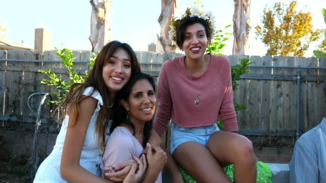 ms portrait of smiling adult daughters and mother sitting together during backyard family barbecue - unity stock videos & royalty-free footage