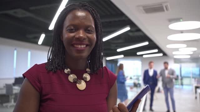 vídeos de stock e filmes b-roll de portrait of smiling african american businesswoman working in modern office - plano charriot