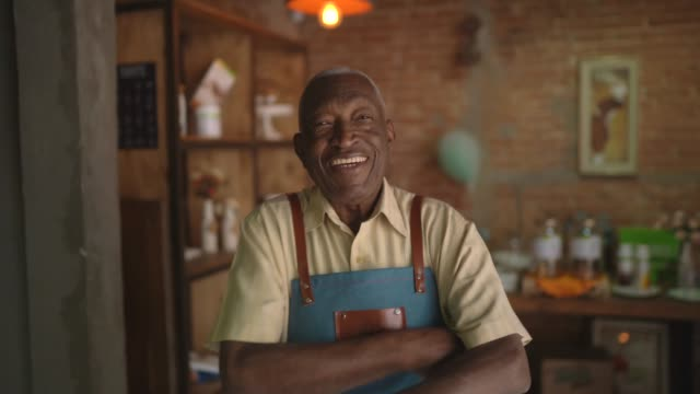 portrait of smiling african elderly waiter looking at camera - part of a series stock videos & royalty-free footage