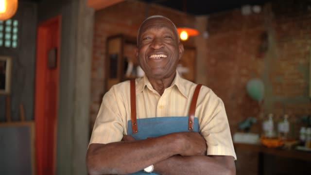 porträt eines lächelnden afrikanischen alten kellners, der in die kamera schaut - gastwirt stock-videos und b-roll-filmmaterial