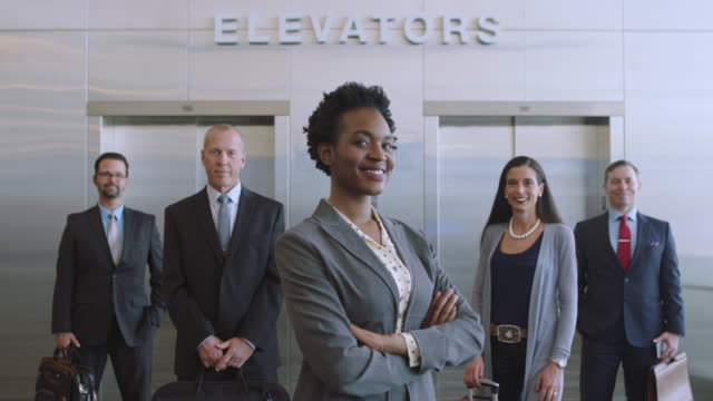 slo mo. portrait of smiling african-american businesswoman and colleagues. tilt up. - global village stock videos & royalty-free footage