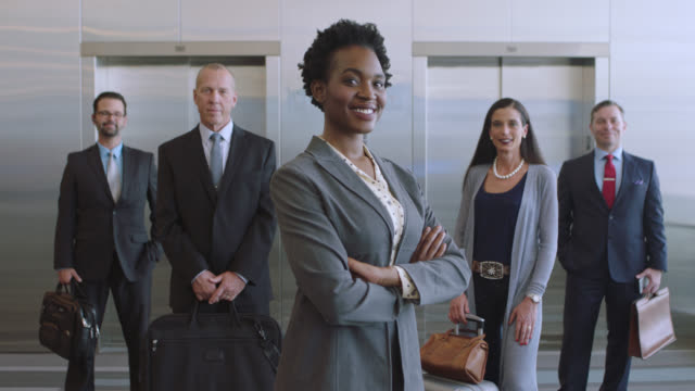slo mo. portrait of smiling african-american businesswoman and colleagues. - confidence stock videos & royalty-free footage