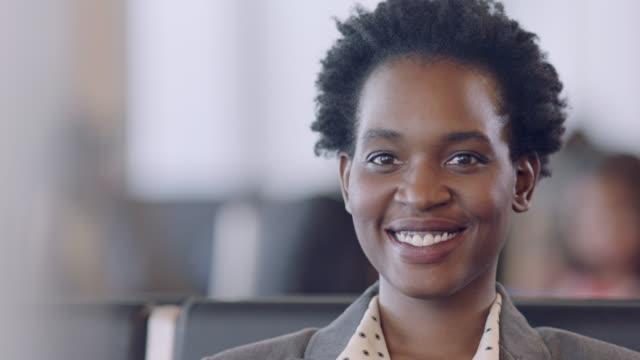 vídeos de stock e filmes b-roll de slo mo. cu. portrait of smiling african-american businesswoman seated in airport terminal waiting area. - tripulação
